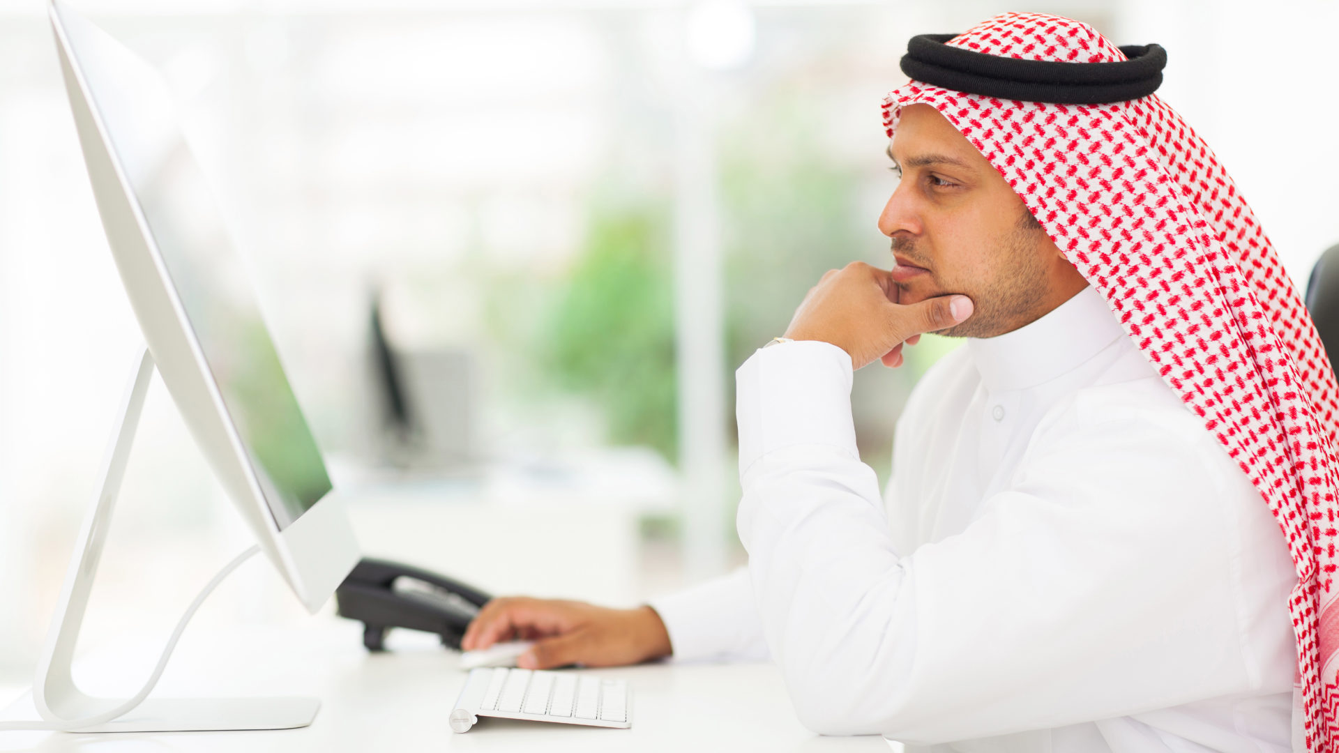 middle eastern businessman looking on a computer screen, sitting in his office